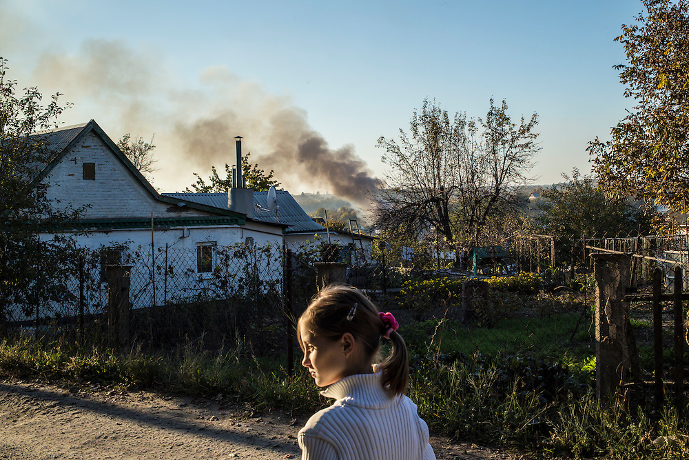 Yeva, 10, walks in the Krasnopillia district at the end of the long trip from the Good News Evangelical Church to the home where she, her mother, and her grandmother are living with a family that is part of the church's congregation on October 12, 2014 in Dnipropetrovsk, Ukraine. Yeva and her family fled fighting in Luhansk. The United Nations has registered more than 360,000 people who have been forced to leave their homes due to fighting in the East, though the true number is believed to be much higher.