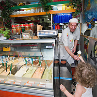 VENICE, ITALY - JUNE 30:    A young customer buys an ice cream from Carlo Pistacchi's Gelateria Alaska in Santa Croce on June 30, 2011 in Venice, Italy. Carlo has been making ice-cream using fresh ingredients for more than 25 years and is renowned for experimenting with new flavours, offering his customers classic favourites such as rum and raisin or chocolate as well as some of his more unconventional creations such as asparagus or rocket salad and orange.