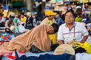 "14 JANUARY 2014 - BANGKOK, THAILAND: A Thai protestor sleeps on the sidewalk at the Victory Monument protest area. Tens of thousands of Thai anti-government protestors continued to block the streets of Bangkok Tuesday to shut down the Thai capitol. The protest, ""Shutdown Bangkok,"" is expected to last at least a week. Shutdown Bangkok is organized by People's Democratic Reform Committee (PRDC). It's a continuation of protests that started in early November. There have been shootings almost every night at different protests sites around Bangkok, but so far Shutdown Bangkok has been peaceful. The malls in Bangkok are still open but many other businesses are closed and mass transit is swamped with both protestors and people who had to use mass transit because the roads were blocked.     PHOTO BY JACK KURTZ"
