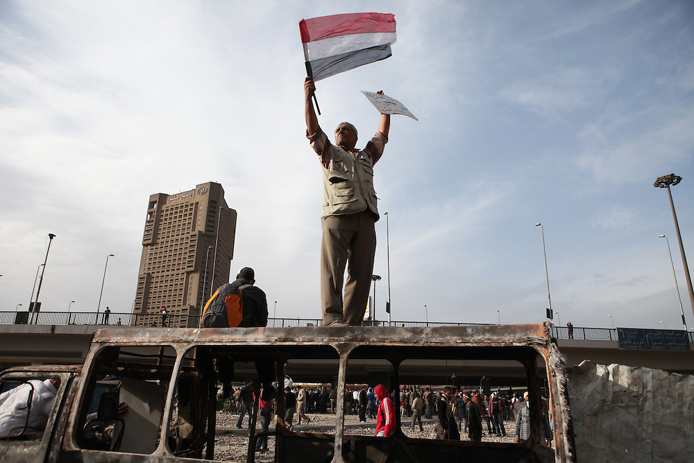 Pro-democracy protesters were forced to defend their sit-in protest at Tahrir Square when plainclothes security officers and supporters of then President Hosni Mubarak attacked on 2 February. The street battles lasted almost two days before Mubarak's forces were driven away. A pro-democracy protester carries an Egyptian flag in a battle with Mubarark's forces near Tahrir Square on 3 February.
