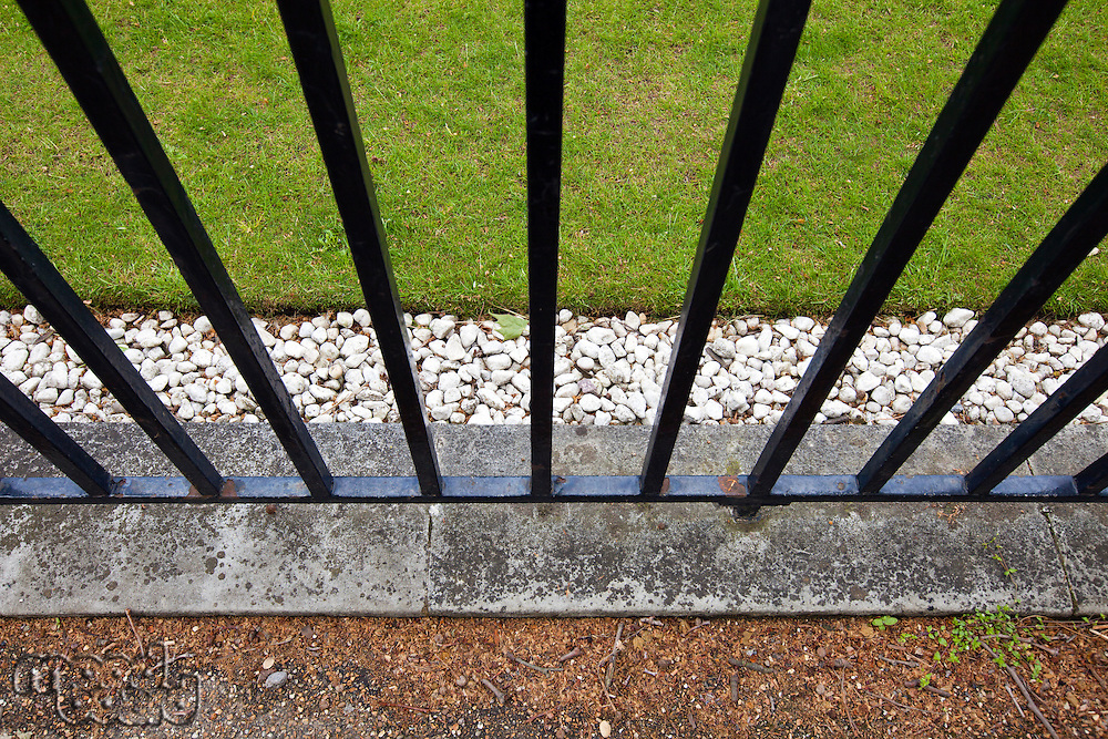 Iron fence, grass and pebbles