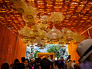 22 OCTOBER 2017 - BANGKOK, THAILAND: People walk through a tunnel of marigolds in front of Pak Khlong Talat, the flower market, in Bangkok. There is a replica crematorium south of the flower market and the street in front features elaborate displays in the late king's honor. The King died in October 2016 and will be cremated on 26 October 2017.     PHOTO BY JACK KURTZ