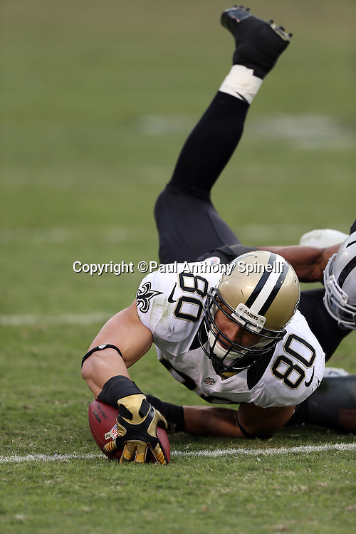 New Orleans Saints tight end Jimmy Graham (80) catches a fourth quarter pass and gets tackled by Oakland Raiders strong safety Mike Mitchell (34) during the NFL week 11 football game against the Oakland Raiders on Sunday, Nov. 18, 2012 in Oakland, Calif. The Saints won the game 38-17. ©Paul Anthony Spinelli