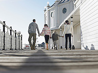 Family holding hands walking along pier back view low angle view