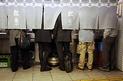 Many office workers stand behind curtain screen at  small bar in Japanese railway station