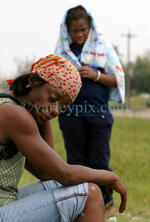 29 August 2006. New Orleans, Louisiana. Lower 9th ward. Great Flood commemoration and memorial ceremony; to 'honor and remember our loved ones who have passed.' <br /> A mourner sits in silence, deep in thought, mourning the loss of her uncle in the  Lower 9th ward as she remembers her own struggle to survive the waters that day a year ago.<br /> Photo Credit©; Charlie Varley/varleypix.com