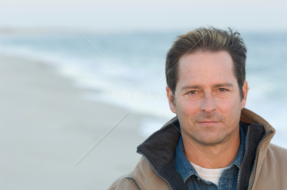 good looking man at the beach in layered clothing