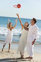 Bride throwing bouquet on beach