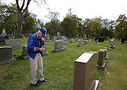 "78-year-old Cubs fan Bob Zondor of Highland, Ind., prays at the grave of his father John E. Zonder. Zondor visited the grave to pray and place a Cubs sticker on his father's headstone. ""I just wish he were here to see this,"" Zonder said about his father who was a devoted Cubs fan."