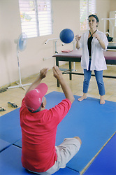 Man in Cuban clinic playing ball with physiotherapist as coordination exercise,