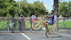 With yellow helmet, Kelvyn Anderson watches how one young rider pulls his BMX bike in a wheelie. (Bastiaan Slabbers/for NewsWorks)