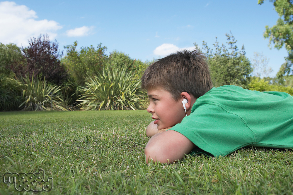 Boy (10-12) lying on elbows in grass listening to mp3 player