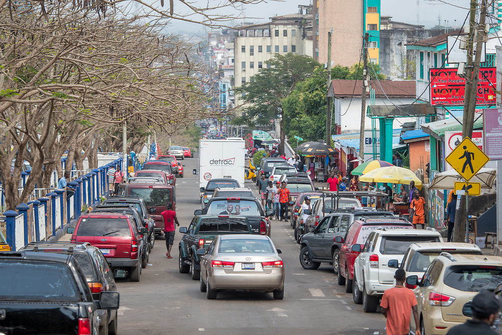 Cars drive down a crowded street in the bustling city of Monrovia, Liberia