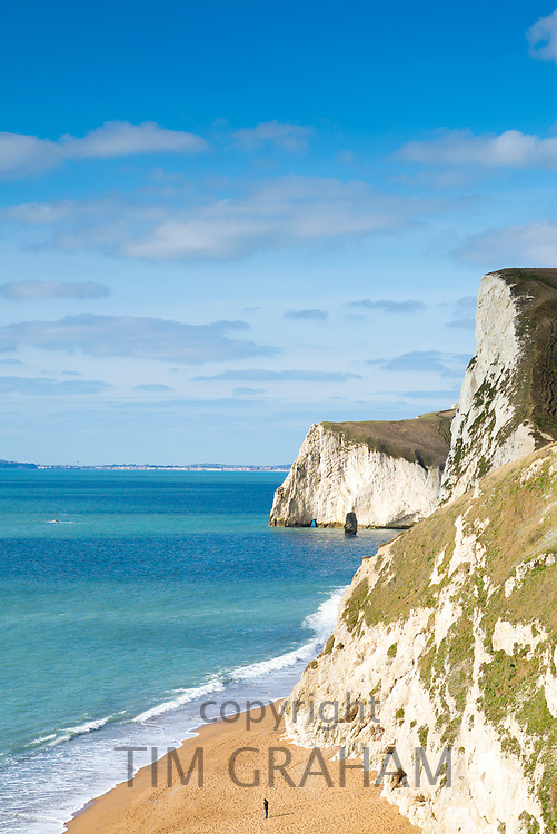 Single figure on the beach by limestone cliffs of the Jurassic coast towards Bat's Head near Lulworth, Wareham, Dorset, UK