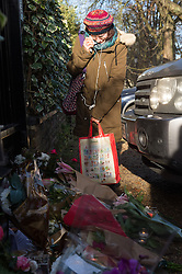 © Licensed to London News Pictures. 26/12/2016. A well wisher leaves a floral tribute outside the Highgate home of singer GEORGE MICHAEL who died of heart failure at his Oxfordshire home aged 53. London, UK. Photo credit: Ray Tang/LNP