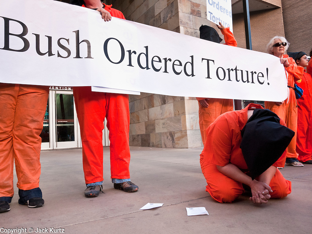 "16 MARCH 2011 - PHOENIX, AZ:  A person portraying a ""Gitmo"" detainee protests against former President Bush's policies of ""enhanced"" interrogation and rendition at the entrance to the Phoenix convention center before Bush spoke inside Wednesday. Former president George W. Bush spoke at Arizona Christian University's 50th anniversary dinner at the Phoenix Convention Center Wednesday night. Hundreds of people from progressive and social justice groups demonstrated against the former president. PHOTO BY JACK KURTZ"