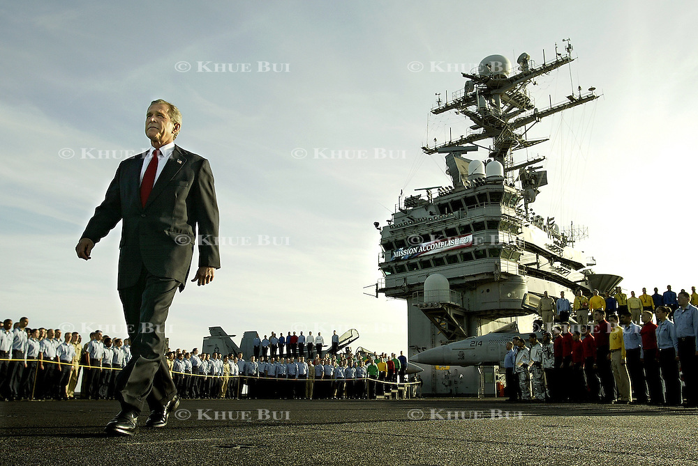 President Bush walks across the flight deck of the aircraft carrier USS Abraham Lincoln to address the nation Thursday, May 1, 2003, in the Pacific Ocean.  Bush traveled to the aircraft carrier USS Abraham Lincoln to meet with returning sailors and to announce and end to 'major combat operations' in Iraq.  The banner in the background says 'Mission Accomplished'..Photo by Khue Bui