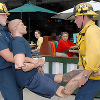 Santa Monica Firefighters Joe Cavin (left) and Jim Schier demonstrate how to properly move an injured victim during the Great Southern California Shakeout, a statewide earthquake drill, at the Third Street Promenade on Thursday, October 21, 2010.