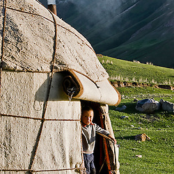 Kyrgyz boy at the yurt door. Kyrgyz mountains.