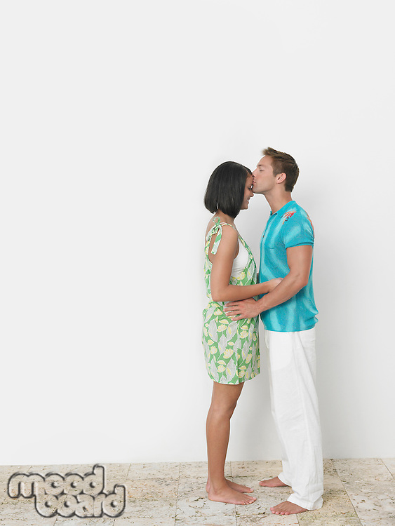 Loving young man kissing woman's forehead against wall