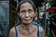 """Portrait of Lucia Abletes, mother of Junnar Abletes, 27, who was gunned down in Duterte's """"War on Drugs"""" when he returned for a family visit from the island of Samar.  Lucia did not believe it was safe for him to be in Market 3 slum, even though he had stopped using drugs.  Her worries were confirmed.  Junmar leaves behind a young son that she will now raise.  Market 3 slum, Navotas, Metro Manila, Philippines"""