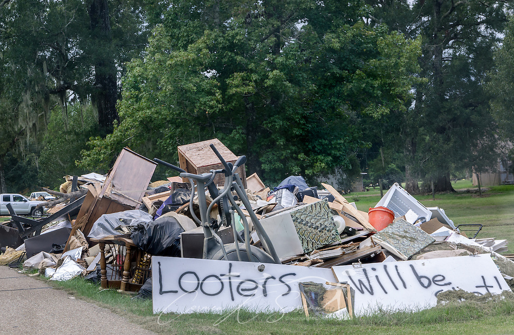 A hand-painted sign warns would-be looters that they will be shot if they steal from a pile of flood debris, Sept. 4, 2016, in Denham Springs, Louisiana. Officials estimated that 90 percent of the homes in the city flooded due to heavy rain in mid-August 2016. The 2010 Census reported a population of 10,215 people. (Photo by Carmen K. Sisson)