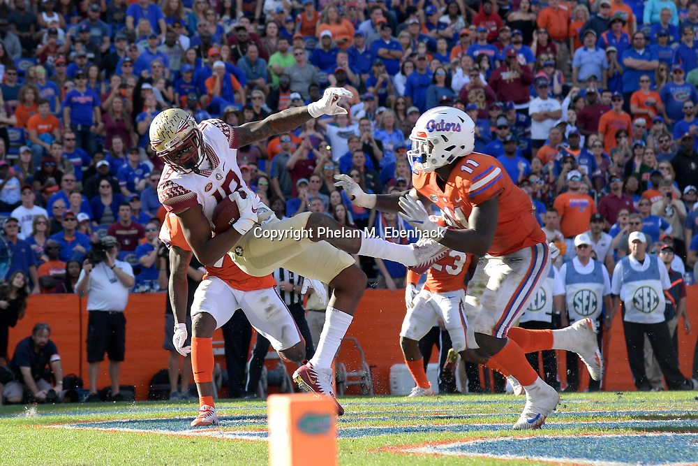 Florida State wide receiver Auden Tate (18) catches a pass in the end zone for a three-yard touchdown in front of Florida defensive back Duke Dawson (7) and linebacker Vosean Joseph (11) during the second half of an NCAA college football game Saturday, Nov. 25, 2017, in Gainesville, Fla. FSU won 38-22. (Photo by Phelan M. Ebenhack)