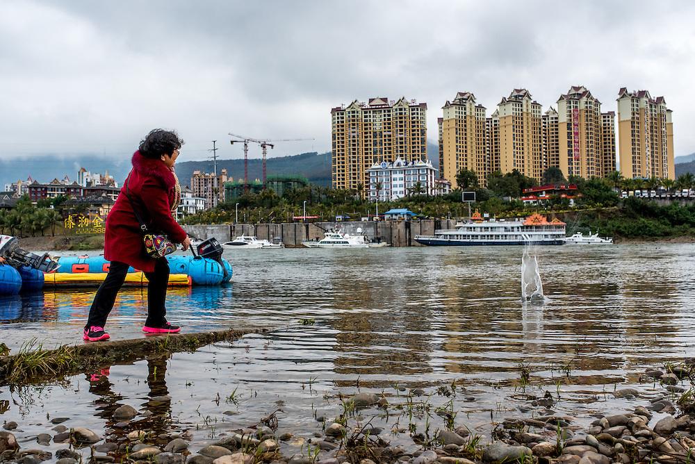 A woman skips stones on the Lancang (Mekong) in Xishuangbanna, Yunan, China.