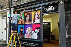 © Licensed to London News Pictures. 22/06/2020. LONDON, UK. A worker paints the exterior of a pop-up shop in Carnaby Street selling facemasks from a vending machine to the public by London-based company Maskey.  Established by entrepeneur Adam Freeman to address the demand for affordable UK-made facemasks during the ongoing coronavirus pandemic, the newly established company is installing the UK's first fashionable face mask vending machines in locations around London, with plans to expand further.  10% of the profit from each facemask sale is donated to a charity supporting the NHS.  Photo credit: Stephen Chung/LNP