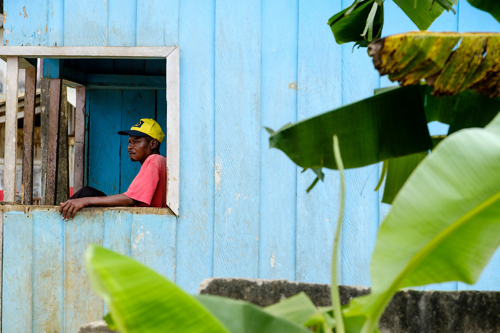 A man in the verandah of his colorful wooden house in Príncipe island, in São TOmé e Príncipe archipelago.