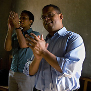 Helene Gayle, CEO and President of CARE and Congressman Keith Ellison dance during the start of a meeting with members of the Barracka HIV/AIDS support group in South Alego village. The group is comprised of 35 women and 15 men who are HIV positive who have come together to support each other and help reduce HIV prevalence in the community.