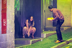© Licensed to London News Pictures . 01/01/2016 . Manchester , UK . A woman squats in a doorway and urinates . Revellers in Manchester on a New Year night out at the clubs around the city centre's Printworks venue . Photo credit : Joel Goodman/LNP