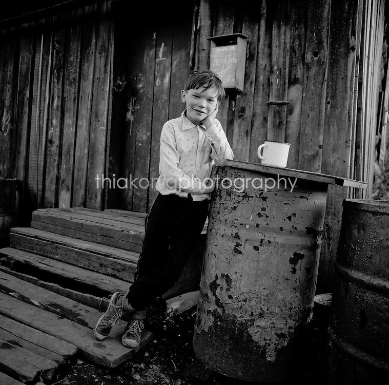 Black and white portrait of boy on back porch, 11pm at night - land of the midnight sun, Turhohansk, Siberia, Russia