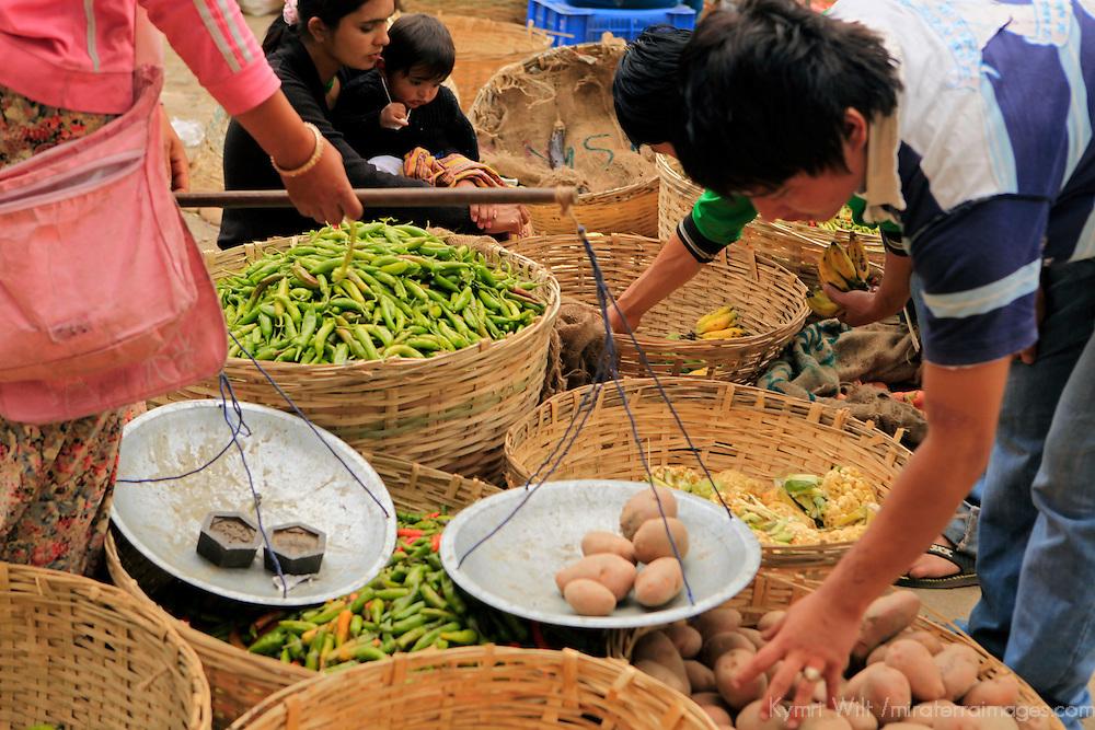 Asia, Bhutan, Wangdue Phodrang. Selecting potatoes at Wangdue market.
