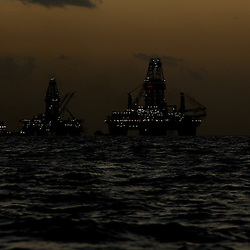 The Transocean Development Driller III and Transocean Development Driller II are silhouetted along with vessels leased by BP Plc after sunset at the BP Plc Macondo well site in the Gulf of Mexico off the coast of Louisiana, U.S., on Thursday, July 29, 2010. BP Plc continues to work on a relief well to permanently plug the source of the largest oil spill in U.S. history.  Photographer: Derick E. Hingle/Bloomberg