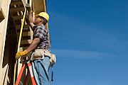 Construction worker measuring half constructed doorway with tape measure