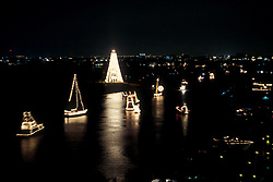 Boats on the water at night with Christmas lights and decorations