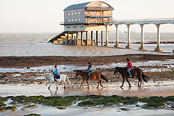© Licensed to London News Pictures. 27/12/2014. Bembridge, Isle of Wight, UK. People riding horses riding along Lane End Beach on the Isle of Wight this morning, 27th December 2014. The South of England is expected to experience clear skies with a strong wind for the weekend. Photo credit : Rob Arnold/LNP