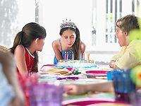 Girl (10-12) blowing out birthday candles at party