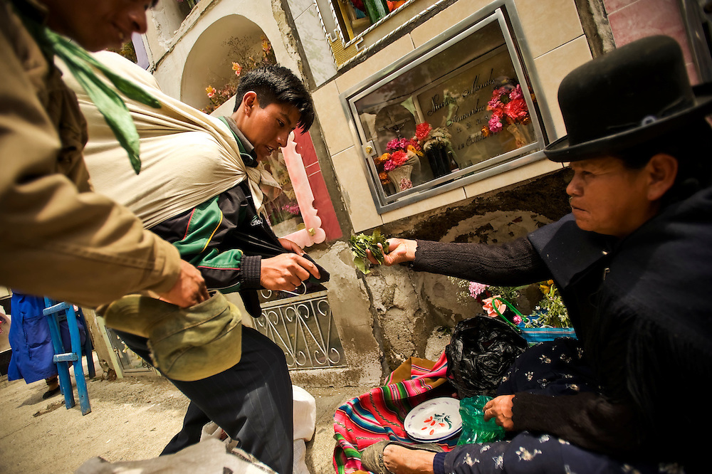 A woman pays men that prayed for her dead husband with dried coca leaves on Day of the Dead at General cemetery in La Paz, Bolivia. Coca, the plant used to make cocaine, is also widely used in Bolivia for traditional purposes, such as tea and for chewing as a mild stimulant. On Day of the Dead, many people came to the cemetery and left flowers, baked goods, and dried coca leaves for their dead relatives.
