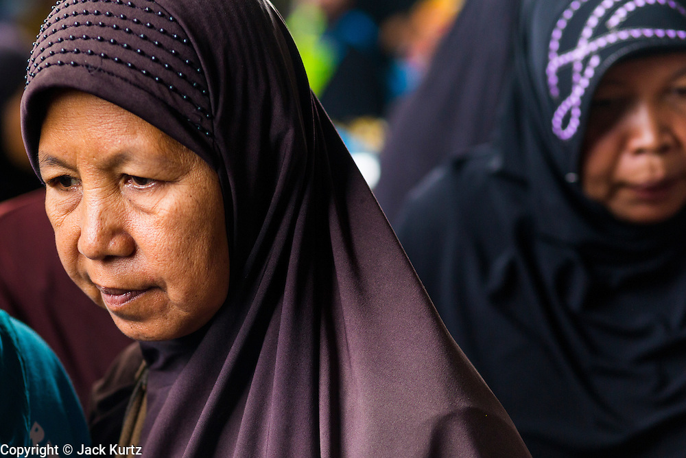 09 JULY 2013 - PATTANI, PATTANI, THAILAND:  Muslim women walk through the market in Pattani.  Pattani, along with Narathiwat and Yala, are the only three Muslim majority provinces in Thailand.     PHOTO BY JACK KURTZ
