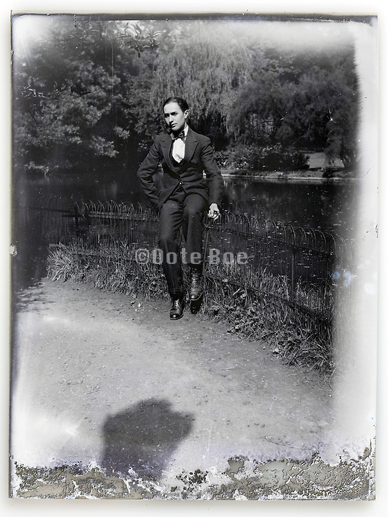 young adult dandy looking man sitting on a fence in the garden Paris early 1900s