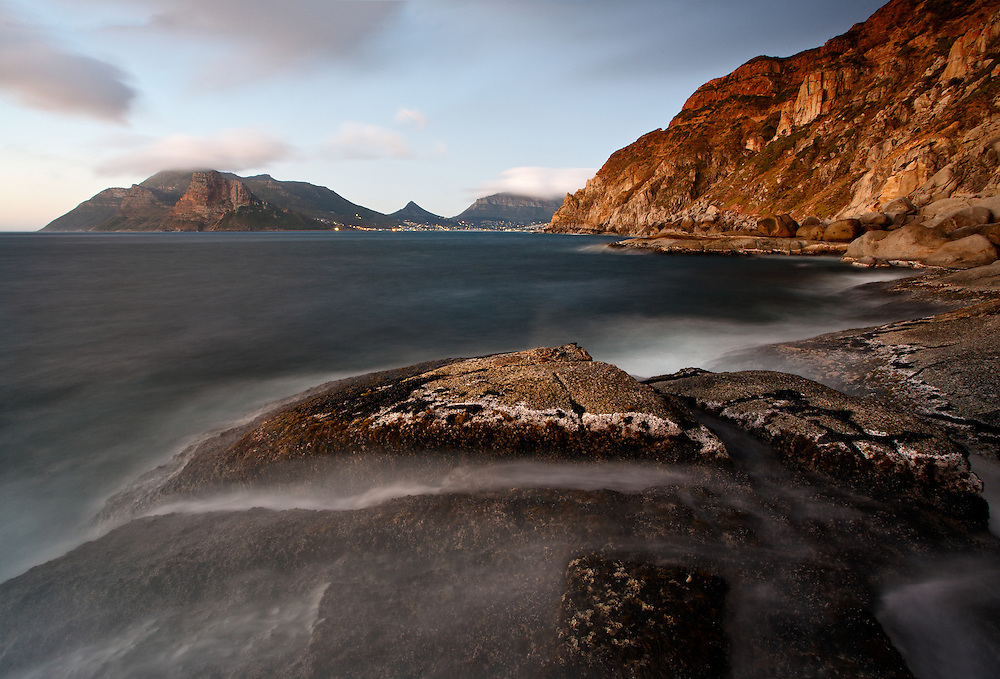 A long exposure rendering of a peaceful and beautiful twilight coastal scene with a view of the lights of Hout Bay and Chapmans Peak, Cape Province, South Africa.