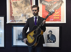A staff member holds a guitar once owned by Jimi Hendrix on display ahead of the the Entertainment Memorabilia Sale at Bonhams in Knightsbridge, London later this week.