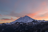 Last bit of sunset light on the clouds above Mount Baker (Komo Kulshan) after the sun has set on the Mount Baker-Snoqualmie National Forest of Washington State. Photographed from Huntoon Point on Kulshan Ridge.