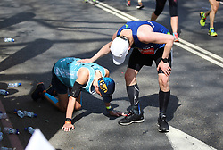 © Licensed to London News Pictures. 22/04/2018. London, UK. A man is helped by a fellow runner during the 2018 London Marathon which is being run in unusually warm temperatures for April. This years event is being started by HRH Queen Elizabeth II. Photo credit: Tom Nicholson/LNP