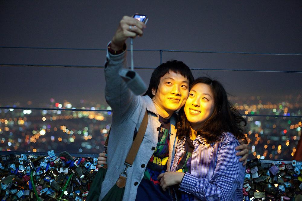 Junges Paar fotografiert sich in abendlicher Stimmung auf der unteren Aussichtsplattform des N Seoul Towers in der koreanischen Haupstadt umringt mit W&uuml;nschen versehenen Schl&ouml;ssern. Der N Seoul Tower ist ein der &Ouml;ffentlichkeit zug&auml;nglicher Fernsehturm in der s&uuml;dkoreanischen Hauptstadt Seoul. Der 236,7 Meter hohe Turm steht auf 243 m &uuml;. N.N. des Berges Namsan.<br /> <br /> Young couple photographing each other during an evening mood at the lowest observation deck of the N Seoul Tower surrounded by lockers. N Seoul Tower is a communication tower located in Seoul, South Korea. Built in 1969, and opened to the public in 1980, the tower measures 236.7 m (777 ft) in height (from the base) and tops out at 479.7 m (1,574 ft) above sea level.