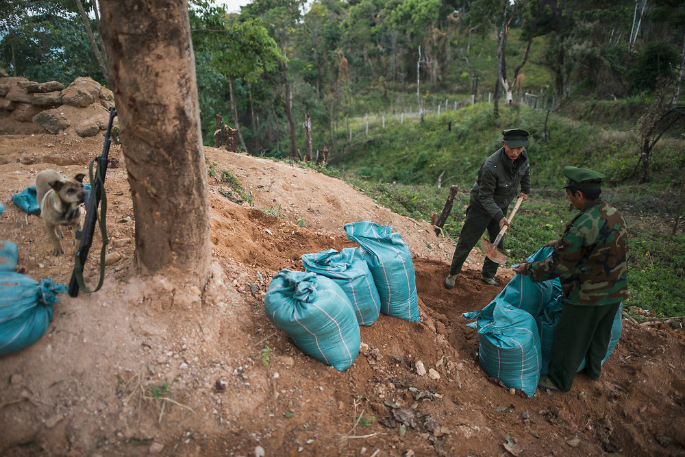 KIA Mobile Brigade, Myanmar 20180124 <br /> Aung Lun and Naw San, Kachin Independence Army Soldiers, reenforcing their positions with sandbags at a frontline outpost just 1 km from the Burma Armys nearest outpost. Manji the dog is inspecting the rifles.<br /> Photo: Vilhelm Stokstad / Kontinent