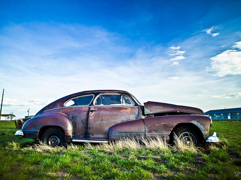 A vintage coupe sits rusting in a field on the Wyoming Highway 287 alignment of the Lincoln Highway in central Wyoming. The original alignment is remote with little traffic, affording vast views of empty sky and abandoned cars and buildings. <br /> <br /> /// ADDITIONAL INFORMATION: 5/24/11 - travel.Lincoln.East.0929.sp - STUART PALLEY Lincoln Highway West