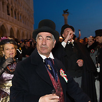 "VENICE, ITALY - FEBRUARY 19:  Members of the association ""Amici del Carnevale di Venezia"" wearing 19th century costumes enjoy live music in St Mark Square on February 19, 2011 in Venice, Italy. The fountain pouring wine features today during the Gran brindisi a Venezia or Grand Toast in Venice, the opening ceremony of this year Carnival ."